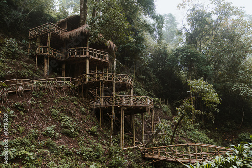 Poster Khaki Wooden bamboo hovel house in forest. Film color toned filter