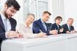 Geschäftsleute schreiben eine Prüfung
