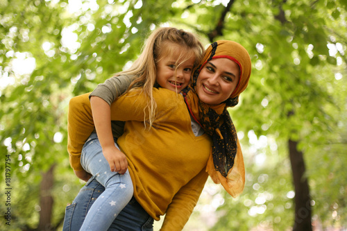 Mother carrying daughter on piggyback. Muslim.