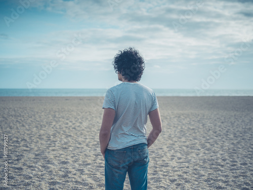 Young man standing on the beach