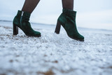 Female boots on fresh ice crystals - 181800513
