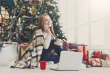 Young woman shopping online in cozy christmas interior - 181802526