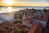 Sunset over the old mediterranean city near the seacoast of Adriatic sea. Aerial landscape of beautiful red roofs of Zadar, Croatia - 181802939