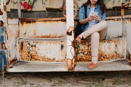 Poster Young woman sitting and using smartphone on a bus wreck.