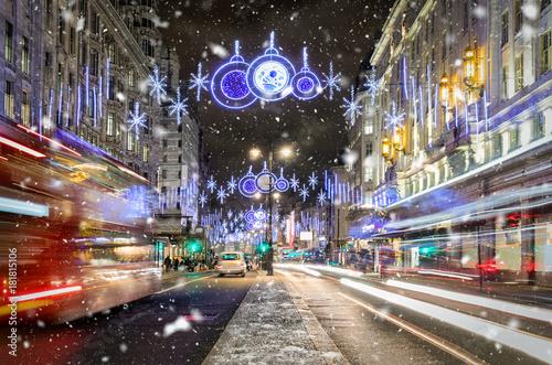 Festlich geschmückte Einkaufsstraße in London mit vorbeifahrendem Bus und Schneefall