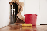 Damaged wall, exposed burst water pipes, sponge and bucket - 181815903