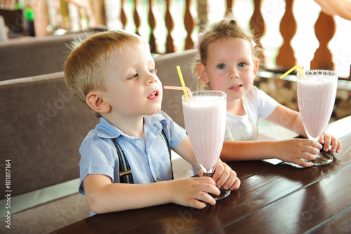 Foto op Plexiglas Milkshake Little boy and girl drinking milkshakes in a cafe outdoors.