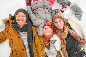 winter family lying in snow