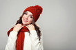 Beautiful young girl in sweater, scarf and hat on grey background