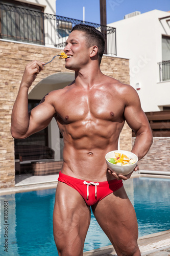 Muscular young sexy wet guy in a speedo eating fruit near the pool outdoors Plakát
