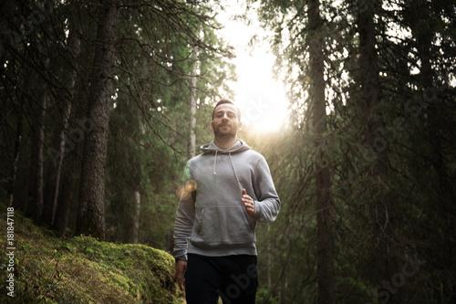 Fotobehang Hardlopen Man joggt im Pullover durch den Wald
