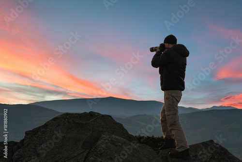 Foto op Canvas Blauwe jeans Man taking picture of beautiful sunset in mountains