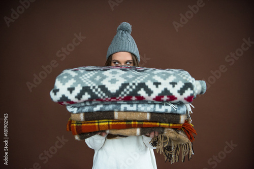 Woman looking out from pile of blankets