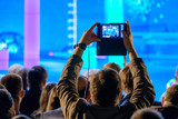 Man takes a picture of the presentation at the conference hall using smartphone - 181906725