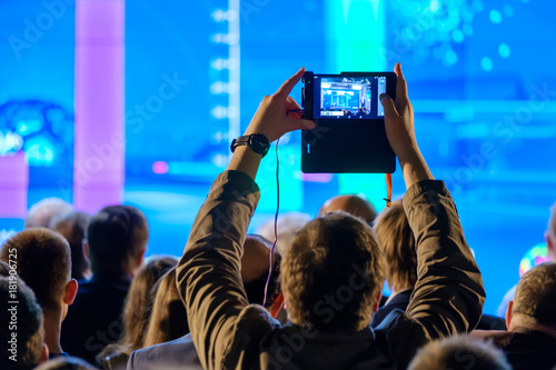 Man takes a picture of the presentation at the conference hall using smartphone Poster