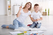 Quadro Mother with cute boy painting picture on sheet of paper, indoors