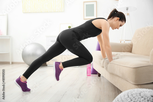 Young sporty woman doing exercise at home