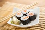 Vier Maki Sushi mit Lachs auf Teller an Holz Stäbchen © Christin