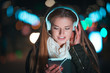 Woman with headphones using tablet and listening music in city at night - 181926307