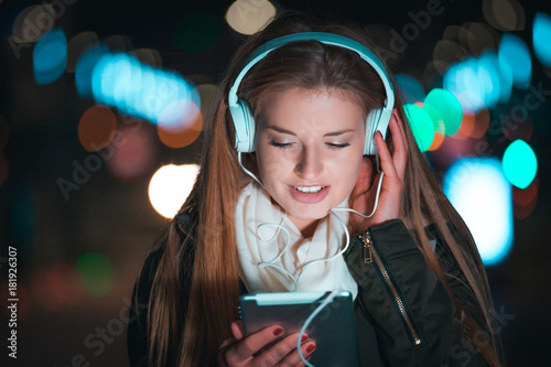 Sticker Woman with headphones using tablet and listening music in city at night