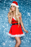 Beautiful sexy blonde female model dressed in a Santa Claus hat and dress. Sensual girl for Christmas. - 181934103