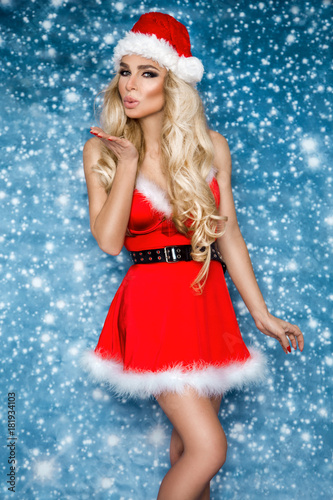 Beautiful sexy blonde female model dressed in a Santa Claus hat and dress. Sensual girl for Christmas.