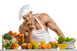 Man bodybuilder in white toque blanche and cook protective apron eat apple