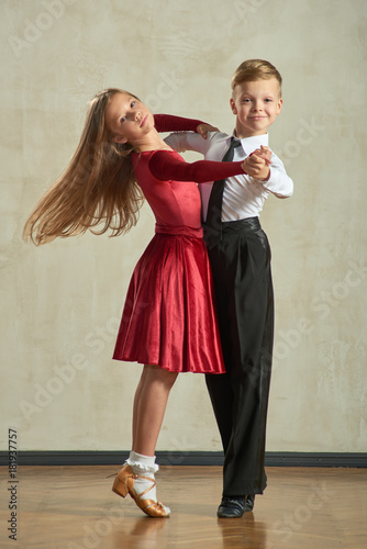 Fototapeta Attractive young couple of children dancing ballroom dance in studio