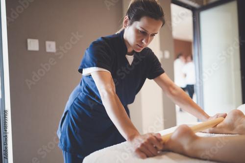 Sticker Massage therapist using wooden tool to massage patient