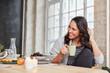 Lachende junge Frau mit Tasse Kaffee in Küche
