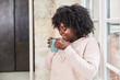 Afrikanische Frau beim Kaffee oder Tee trinken in Küche