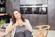 Plus Size Frau sitzt mit Tasse Kaffee in Küche