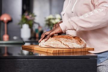 Afrikanische Hände beim Brot schneiden