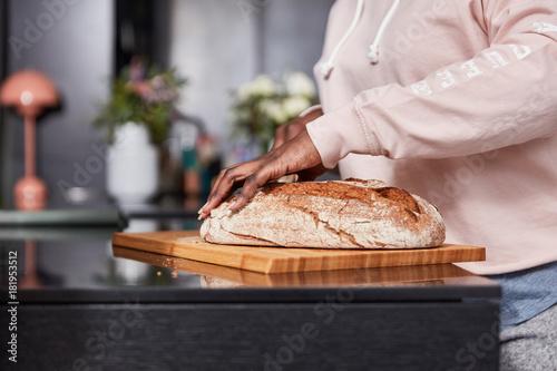Fototapeta Afrikanische Hände beim Brot schneiden