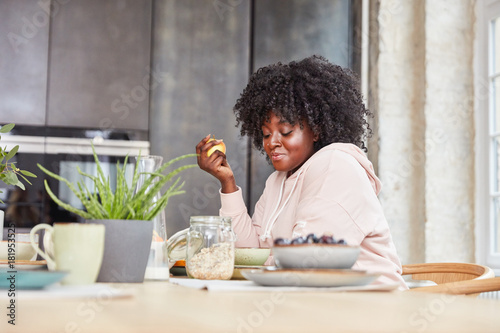 Plus Size Frau isst Apfel zum Frühstück