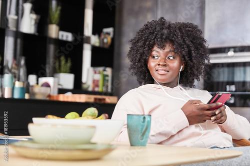 Fotobehang Muziek Afrikanische Frau mit Smartphone hört Musik