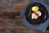 Slices of roast pork with rosemary and potato on a plate, dark rustic wooden background with generous copy space, top view from above - 181972353