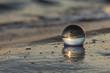 Arte attraverso la sfera di cristallo,sfera adagiata sulla spiaggia e bagnata dal mare.
