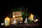 gift boxes in kraft paper and two burning candles decorated with christmas balls, fir branches and small wooden trees on a dark rustic background with copy space - 181972515