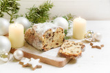 criststollen, typical german christmas cake with candles, baubles and cinnamon star cookies on a rustic white wooden table - 181973571