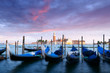 Row of gondolas parked on city pier