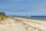scenic beach at island Cape Cod with pier and sailing boat at Chatham