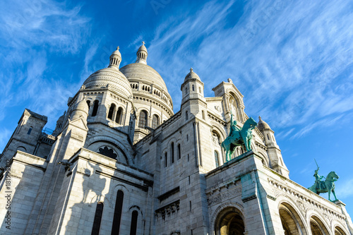 Low angle view of the Basilica of the Sacred Heart of Paris with the two equestrian bronze statues overhanging the portico against blue sky.