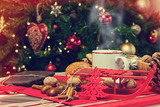 Cup of hot tea on with behind christmas tree. - 181999352