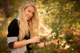 Beautiful blond woman in grey sweater in park on early autumn day - 182003994