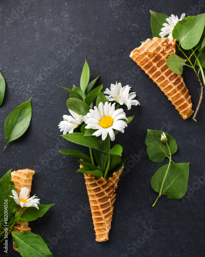 Fotobehang Lelietjes van dalen Ice cream cone with bouquet of chamomiles on a black concrete background. Fresh flowers. beautiful bouquet of wildflowers. Copy Space. space for text. Place for text. Food photo. Flat lay, top view