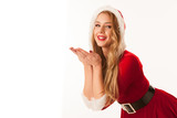 Beautiful young woman in santa dress blows into copy space for christmas isolated over white backgraound - 182004757