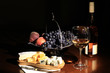 Cheese, wine and fruit on a dark background
