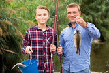 Man with teenager boy showing catch fish - 182008782