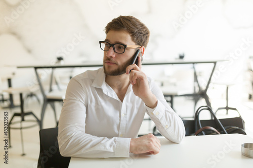 Pensive young businessman in cafe using phone